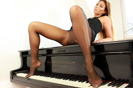 Natalia Forrest playing the piano in tights